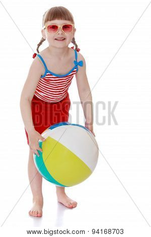 The little girl on the beach with glasses holding a ball