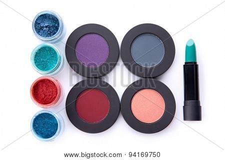Set of loose and pressed eyeshadows, and lipstick, top view isolated on white background with shadow