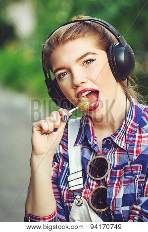 Portrait Of Hipster Girl With Headphones And Lollipop.