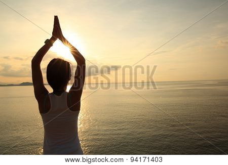 silhouette of young yoga woman at sunrise seaside