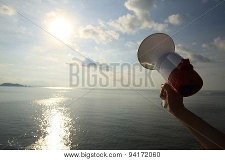 hand hold megaphone  under sunrise seaside twilight sky