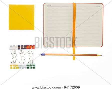 Notebook, pencil  and paper clips on white background
