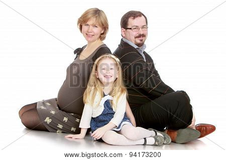 The family of three pregnant mom , dad and little daughter