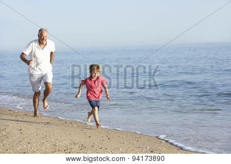 Grandfather And Grandson Running Along Beach