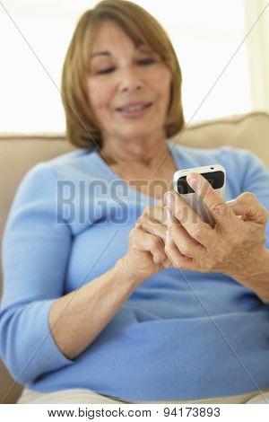 Senior Hispanic Woman Using Smartphone At Home