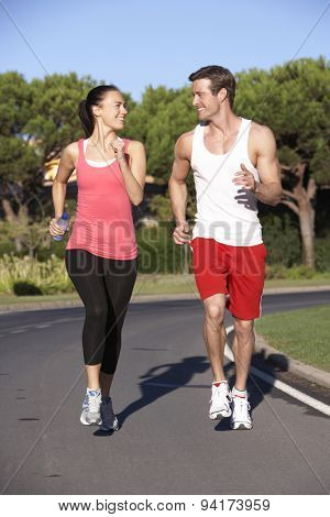 Young Couple Running On Road