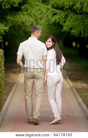 Young Man And Woman Walking In Park