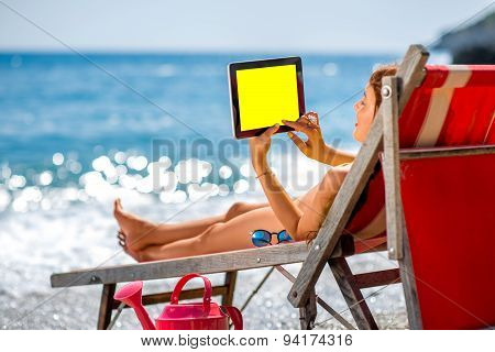 Woman using tablet on the sunbed