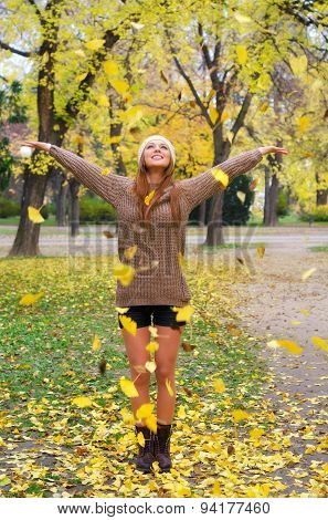 Beautiful Girl Throwing Leaves In The Air In Autumn Forest
