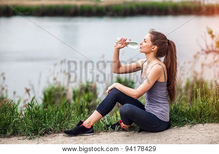Outdoor Photo Of Pretty Young Woman Wearing Sportive Clothes And Drinking Water Sitting Beside A Riv