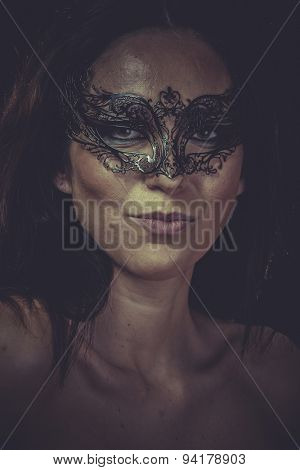Fashion brunette woman in black mask metal frills