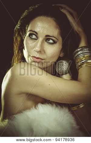 brunette woman wearing white fur and gold jewelry
