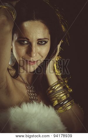 Lady, brunette woman wearing white fur and gold jewelry