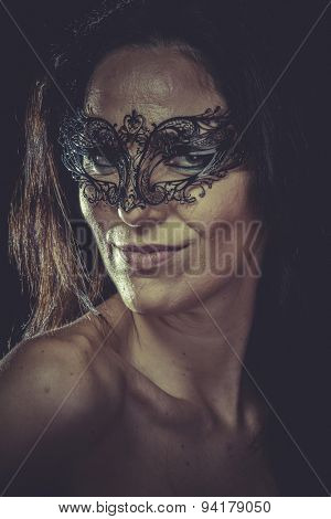Pretty brunette woman in black mask metal frills