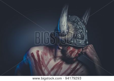 Viking warrior with a horned helmet and war paint on his face