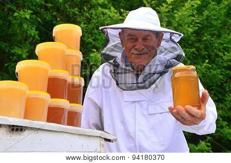 Senior apiarist presenting jar of fresh honey in apiary in the springtime