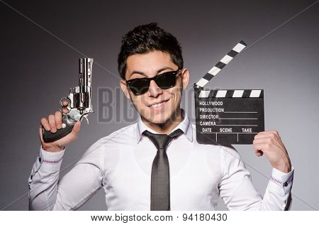 Young man in cool sunglasses holding gun isolated on gray