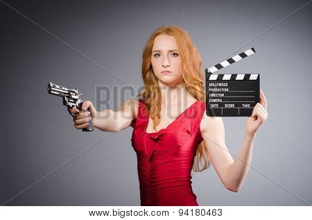Pretty young girl in red dress with gun isolated on white