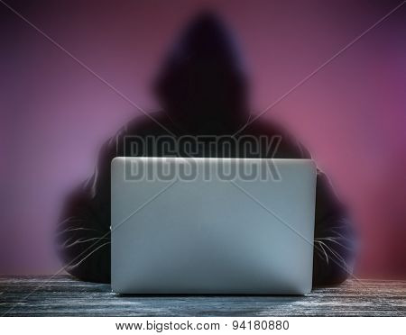 Computer hacker silhouette of hooded man with notebook