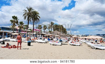 IBIZA, SPAIN - JUNE 19: Sunbathers in the popular Platja den Bossa beach on June 19, 2015, in Ibiza Town, Spain. Ibiza is a well-known summer tourist destination in Europe