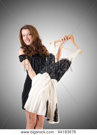 Young woman trying new clothing against gradient