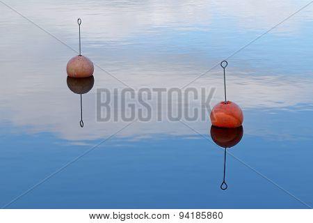 Two Red Buoy Reflecting In Calm Water
