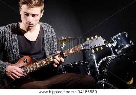 Man playing guitar in dark room
