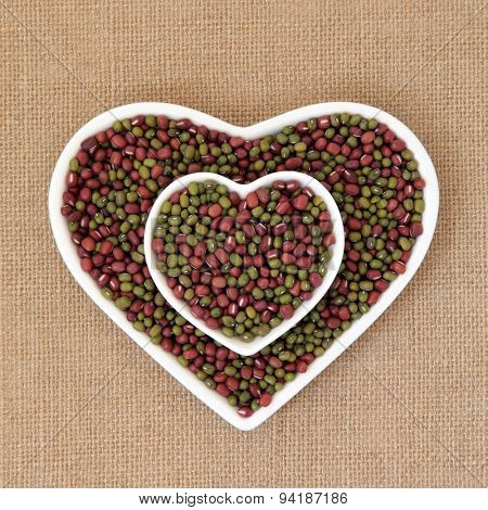 Mung and aduki beans in a heart shaped bowl over hessian background.