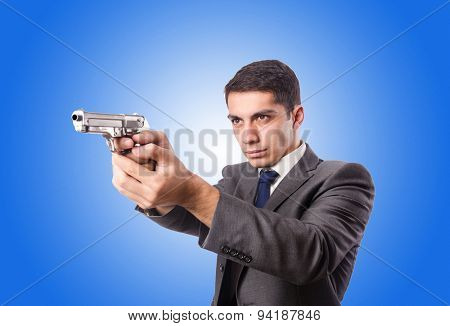 Businessman with gun against the gradient