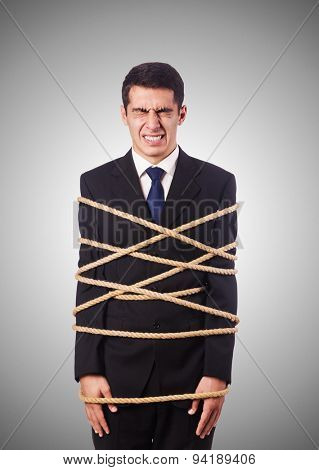 Businessman tied up with rope against gradient