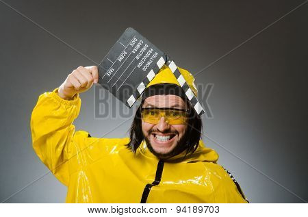 Man wearing yellow suit with movie board