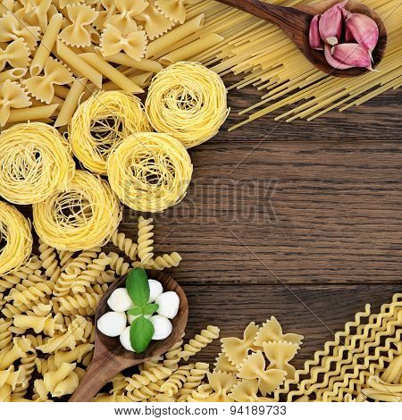 Italian pasta, basil herb, mozzarella cheese and garlic food ingredients forming a background border over oak background.
