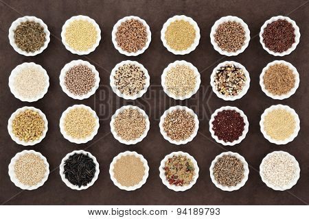 Large cereal and grain food selection in porcelain crinkle bowls over lokta paper background.