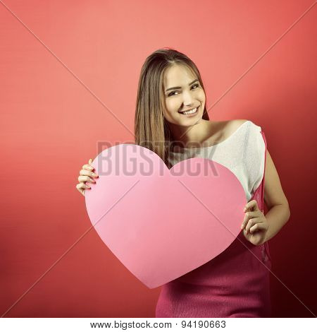 Love and valentines day woman holding heart and smiling over pink background. Beautiful woman in love, image toned.