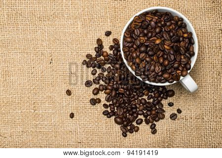 Cup Full Of Coffee Beans Over Cloth Background