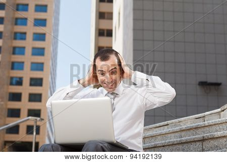 Surprised Business Man Sitting On Steps With Laptop Hods His Head