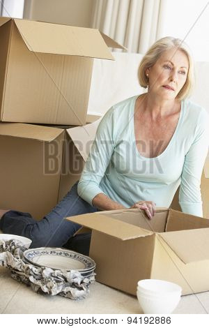 Senior Woman Moving Home And Packing Boxes