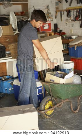 Teenage Boy Clearing Garage For Yard Sale