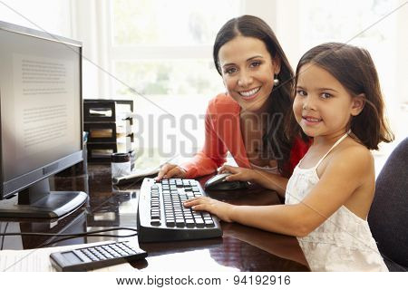 Hispanic mother and daughter using computer at home