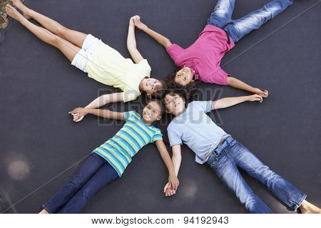 Overhead View Of Group Of Children Lying On Trampoline Together