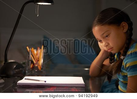 Unhappy Young Girl Studying At Desk In Bedroom In Evening
