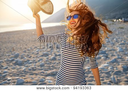 Woman in stripped dress with a hat on the beach
