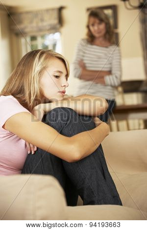 Grumpy Teenage Daughter Sitting On Sofa With Mother In Background