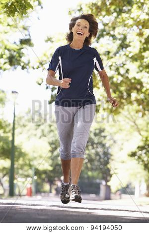 Senior Woman Running Through Park