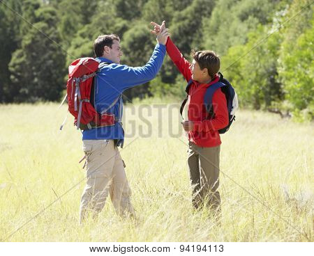 Father And Son On Hike In Beautiful Countryside Giving High Five