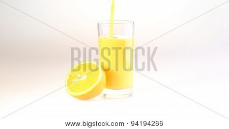 Orange Juice A Stream Flows In A Transparent Glass,a Glass With Orange Juice On A White Background