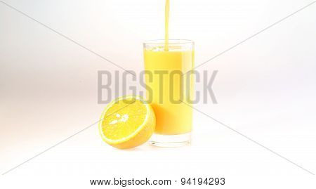 Orange Juice A Stream Flows In A Transparent Glass, A Glass With Orange Juice On A White Background