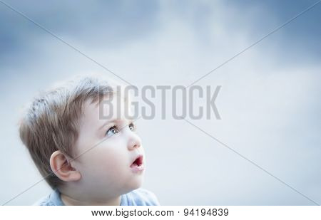 Boy looking at the sky with surprised expression. Imagination of a child
