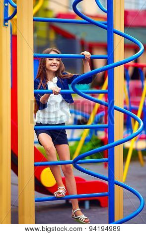 Pretty Kid, Girl Climbs On The Stile At Playground