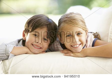 Two Children Relaxing On Sofa At Home